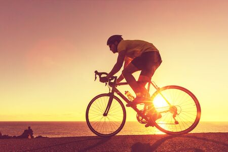 Road bike cyclist sports athlete biking outdoors silhouette near ocean. Professional triathlete riding bike on an open road to the sunset. Active healthy man sport lifestyle. Banco de Imagens
