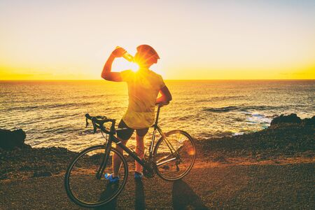 Athlete cyclist man drinking water after intensive biking training, enjoying sunset and ocean. Healthy active lifestyle sports fitness man resting on bike with sun flare.