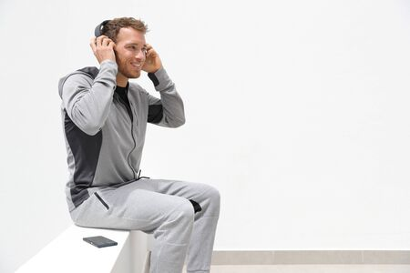 Man listening to music mobile phone app wearing headphones sitting at home. Healthy lifestyle sport athlete using smartphone on jogging break outdoor. Stock Photo