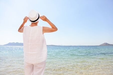 Senior happy woman retired enjoying sun wearing hat on Caribbean beach vacation. Travel tourist standing at sea and clear sky. Rear view of female in casual wearing white linen clothes.