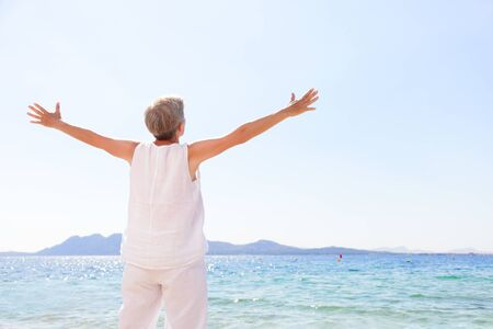 Carefree senior woman standing at beach against clear sky. Rear view of female with arms outstretched is in casuals. Tourist is enjoying summer vacation. Imagens