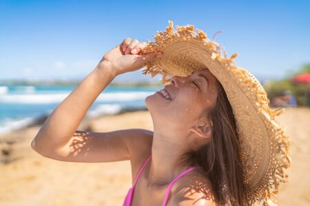 Happy beach woman enjoying summer travel having fun playing with hat on Caribbean holiday vacation. Asian girl playful. Foto de archivo