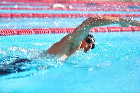 Triathlon-Fitness-Athlet trainiert Cardio-Schwimmen im Außenpool im Stadion. Schwimmermann, der im blauen Wasser schwimmt. Sport- und Fitnessübungen.