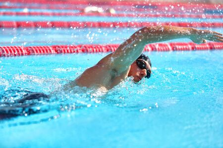 Triathlon fitness athlete man training cardio swimming in outdoor pool at stadium. Swimmer man swmming in blue water . Sport and fitness exercise.