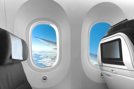 Airplane cabin seat and window view of plane wing on flight travel vacation. LCD screen display for movie entertainment while flying. Empty inside economy class. Stockfoto