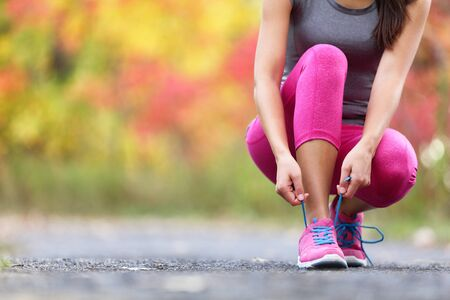 Autumn running shoes girl tying laces ready to run in forest foliage background. Sport runner woman training cardio in outdoor fall nature in pink activewear leggings and footwear. Stock fotó