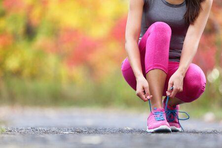 Jesienne buty do biegania dziewczyna wiązanie sznurówek gotowy do uruchomienia w tle liści lasu. Sport biegacz kobieta trening cardio w naturze jesień na zewnątrz w różowe legginsy i obuwie activewear. Zdjęcie Seryjne