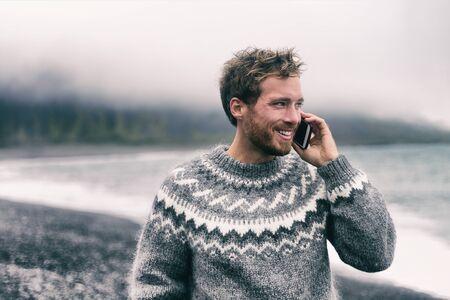 Telefonmann, der auf dem Smartphone im Winterpullover spricht, der am schwarzen Sandstrand in Island spazieren geht. Kleidung aus isländischer Wolle. Technologie-Handy.