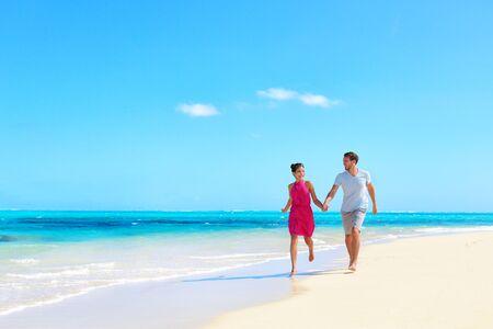 해변 휴가 신혼여행 낙원 - 목가적인 휴가 배경에서 손을 잡고 걷는 사랑에 빠진 젊은 부부.