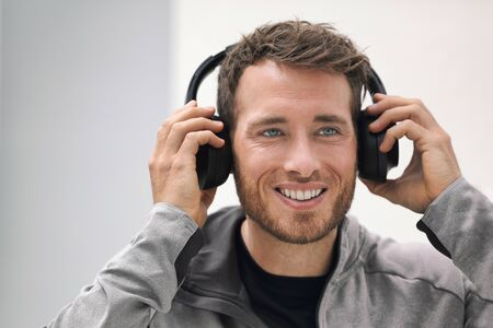 Musik-Kopfhörer-Mann, der online Hörbücher oder Lieder in der Telefon-App hört. Glücklich lächelnde junge Person, die drahtlose Kopfhörer trägt. Junge Erwachsene kaufen ein tragbares Gerät für die Technologie im Laden. Standard-Bild