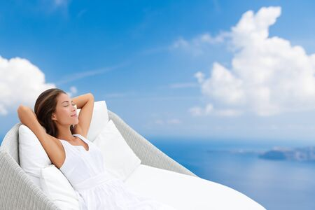 Home lifestyle comfort - woman relaxing sleeping in comfortable sofa chair recliner on blue sky background. Dreaming of wellness, luxury pillows and lounger. Reklamní fotografie