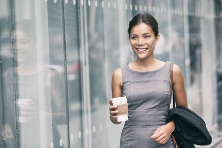 Asian business woman walking going to work drinking coffee to Office building. Successful happy businesswoman commuting in the morning in city street. Stock Photo
