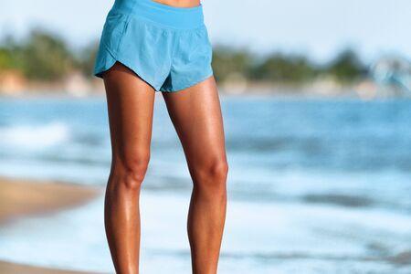 Le gambe della donna si adattano alla ragazza che indossa pantaloncini blu in piedi camminando sulla spiaggia. Raccolto parte inferiore del corpo di gambe toniche e abbronzate. Attraente persona attiva in buona salute.
