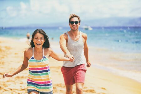Happy young couple laughing on beach summer lifestyle - Spring break fun or summer holidays. Interracial relationship Asian girl, Caucasian man.