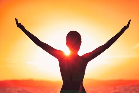 Carefree happiness woman with open arms silhouette in sunset. Success freedom happy life concept in sunrise. Morning yoga girl practicing sun salutation outdoors. Carefree person living a free life.
