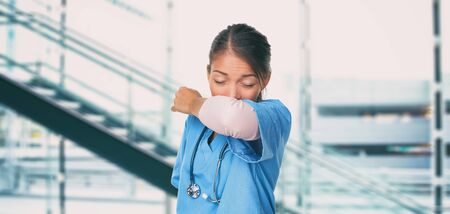 Novel Coronavirus 2019-nCoV hospital nurse or Asian doctor woman worker sneezing into arm covering mouth and nose while coughing flu. Virus protection prevention panoramic banner.