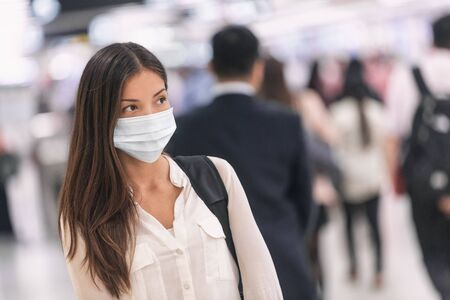Virus mask Asian woman travel wearing face protection in prevention for coronavirus in China. Lady walking in public space bus station or airport. Stok Fotoğraf