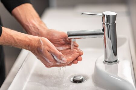 Washing hands man rinsing soap with running water at sink for virus prevention and hand hygiene.