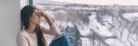 Winter depression sad woman with Seasonal affective disorder girl grief stricken alone at home window thinking negative thoughts. Mental health banner panorama background.