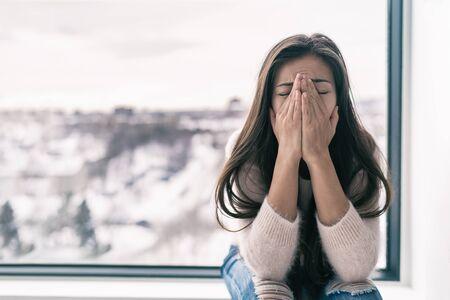 Femme déprimée en état de choc ou de chagrin pleurant seule à la maison se sentant triste avec le trouble affectif saisonnier du blues de l'hiver. Notion de santé mentale. Banque d'images