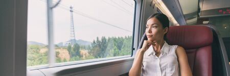 Train travel Asian business woman looking out the window contemplative on morning commute to work commuting banner panorama people lifestyle. Businesswoman in first class seat.