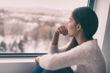 Winterdepression - saisonale affektive Störung psychische Gesundheit Frau traurig kontemplativ allein aus dem Fenster schauen.