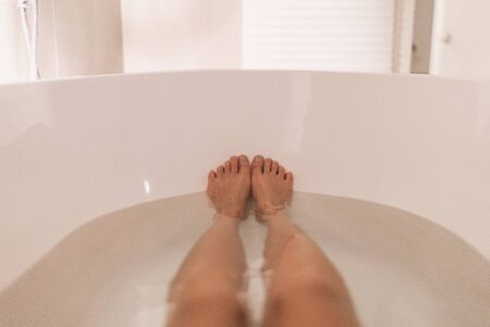 Woman taking a hot bath selfie in tub home cozy relaxation in winter night. POV of feet and legs in water.