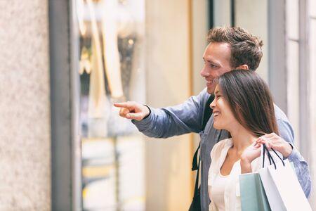 Pareja de compras mirando el escaparate con bolsas de la compra. Comprador de mujer china asiática multirracial y hombre caucásico sonriendo feliz caminando en la calle viviendo en la ciudad. Estilo de vida de la ciudad de la gente. Foto de archivo