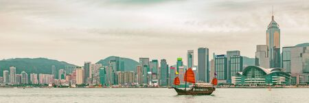 Hong Kong skyline at sunset panoramic banner background with junk boat sailing in sunlight. Foto de archivo