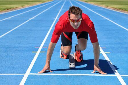 Sport athletics track and field stadium fitness athlete starting race at running tracks ready to run. Runner man going running outside on blue track lanes. Imagens