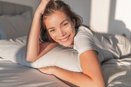 Beautiful Asian woman relaxing at home on pillow bed in bedroom candid smiling portrait. Natural beauty healthy skin model face. 版權商用圖片
