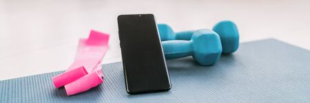 Fitness at home online workout on phone app for training inside with dumbbell weights and resistance bands banner background.