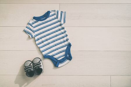 Baby boy outfit newborn onesie clothing with cute little shoes. Clothes in blue stripes style top view on wood floor background.
