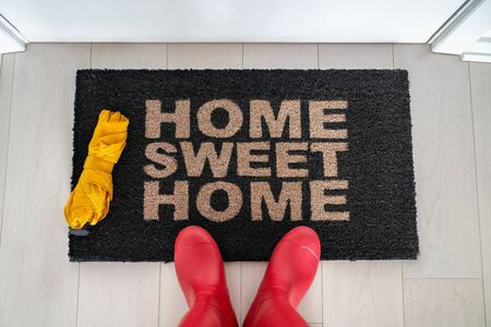 Autumn home sweet home entrance door mat woman taking feet selfie arriving home wiping wet rubber wellington boots and umbrella on rainy day.