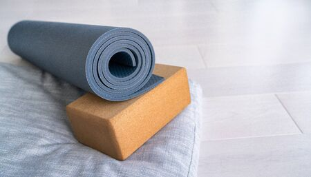 Yoga mat, cork block meditation pillow eco-friendly sustainable fitness products shopping. Natural organic material props for wellness studio on wooden floor background. Standard-Bild