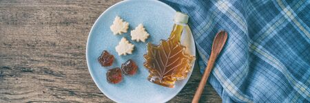 Maple syrup bottle and pure soft sugar candy and taffy top view on kitchen table panoramic banner. Cooking ngredient for desssert recipe, traditonal food from Quebec wood rustic plate panorama. Archivio Fotografico