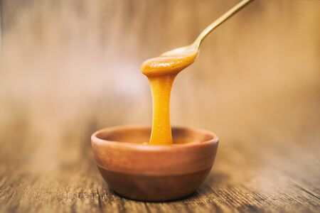 Manuka honey spoon dipped in golden liquid natural superfood on wooden background. Banque d'images