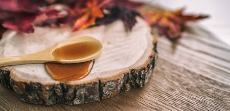 Maple syrup sugar shack cabane a sucre restaurant from Quebec farm maple tree sap famous sweet liquid dripping from wooden spoon on wood log rustic sugar shack banner panoramic with red leaves.