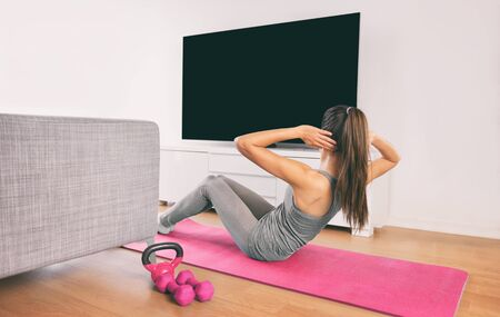 Home fitness woman doing strength training abs situps bodyweight floor exercises watching online livestream workout, web videos casted on smart tv in living room of house or apartment. Banco de Imagens