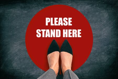 COVID-19 Coronavirus message asking supermarket customer to stand in space. Top view of feet standing in red circle with text in public space practicing social distancing. Blackboard background. Banco de Imagens
