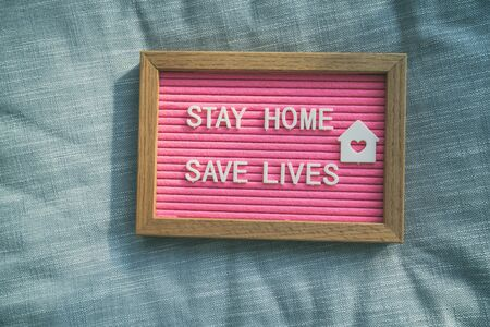 Coronavirus quote stay home, save lives pink felt board sign with message of self isolation for social responsability on home sofa background. COVID-19 text to promote staying at home.