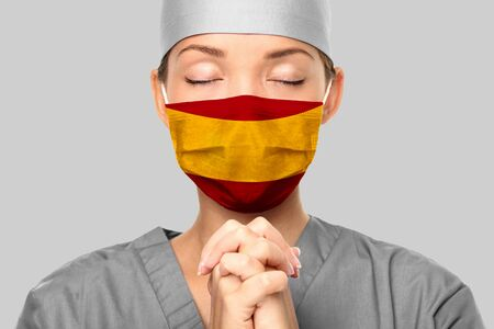COVID outbreak in Spain Asian doctor with spanish flag print on surgical mask praying for help. Young woman medical nurse praying. Coronavirus pandemic in Spain.