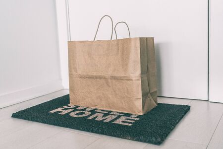 Home delivery of food grocery bag left at door mat for Corona virus spreading safety. Precaution measures against COVID-19, paper bag delivered without contact. Stock Photo