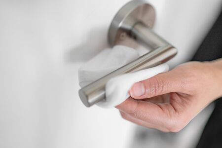 Coronavirus COVID-19 Prevention cleaning woman wiping doorknob with antibacterial disinfecting wipe for killing corona virus on touching surfaces, or touching public bathroom handle with tissue.