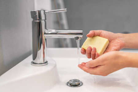 Washing hands with soap. Hand hygiene woman holding bar of soap for COVID-19 corona virus prevention, to stop spreading coronavirus.