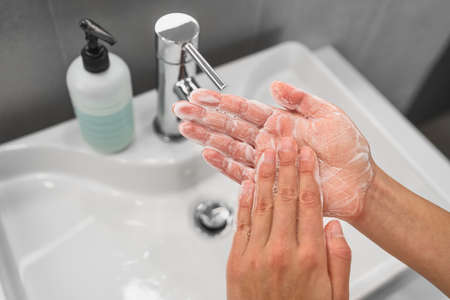 Washing hands rubbing soap in palm with foam bubbles for corona virus COVID-19 prevention. Hand hygiene to stop spreading coronavirus. Woman handwashing in bathroom sink.
