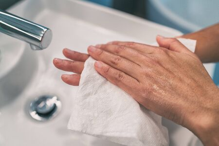 Washing hands steps for personal hygiene COVID-19 prevention drying hand with paper towel after handwash. Coronavirus infection preventive cleaning.
