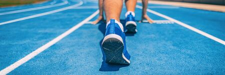 Sprinter fit man waiting for start of race on running tracks at outdoor stadium. Sport and fitness runner athlete on blue run track starting line with running shoes. Banner panorama. Stock Photo
