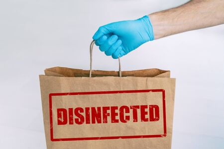 Delivery bag to home from online grocery shopping with stamp of safety DISIFINFECTED written on the paper side. Man holding groceries with medical blue glove.