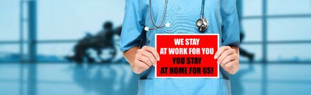 COVID-19 Social distancing quote medical nurse promoting staying at home to help workers. Coronavirus doctor holding sign in hospital background. Panoramic corona virus sign banner with text title. Foto de archivo